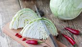 image of cruciferous  - Cutted cabbage on cutting board with red chili peppers and knife on wooden background - JPG