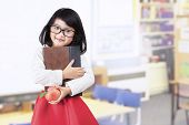 stock photo of indian apple  - Attractive little asian girl holding a book and apple in classroom - JPG