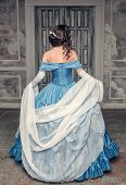 stock photo of pompous  - Beautiful medieval woman in long blue dress back - JPG
