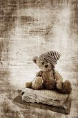 stock photo of teddy-bear  - Grunge background with fur teddy bear in handmade hat sitting on quilts and space for text - JPG
