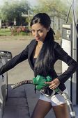 image of fuel economy  - Beautiful elegant young woman fueling pumping gas - JPG