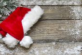 picture of christmas claus  - Santa Claus hat on vintage wooden boards christmas background - JPG
