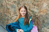 stock photo of pullovers  - Adorable little girl of 7 years old ready to go to school - JPG