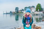 picture of pullovers  - Pretty little girl resting by the lake on a cold cloudy day - JPG