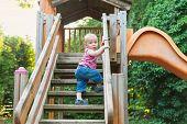 picture of playground  - Adorable toddler boy having fun on playground - JPG