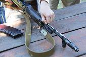 stock photo of kalashnikov  - Female hand harvested Kalashnikov rifle at outdoors - JPG