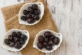 stock photo of ceramic bowl  - Marinated black olives in white ceramic bowl on white wooden background - JPG