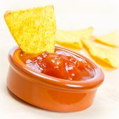 stock photo of nachos  - spicy nachos with tomato salsa close up