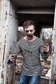 stock photo of insane  - Screaming insane zombie in abandoned empty house - JPG