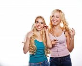 stock photo of flutter  - Beautiful girls sisters headphones listening to music with fluttering hair - JPG