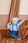picture of suspenders  - Little cute baby in jacket and jeans with suspenders shot in home interior - JPG