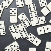stock photo of over counter  - Multiple domino bones composition over the dark gray surface - JPG