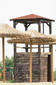 stock photo of lifeguard  - Straw umbrellas and lifeguard watchtower at a beach - JPG