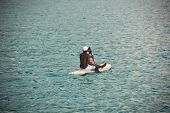 picture of canoe boat man  - Young Seychellois man on a surfboard selling fruits in the middle of the ocean