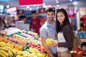 stock photo of supermarket  - Young couple shopping in a supermarket - JPG