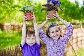 picture of violet  - Happy kids with newly planted violets looking at camera in natural environment - JPG