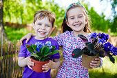 image of environment-friendly  - Friendly boy and girl with garden violets looking at camera in natural environment - JPG