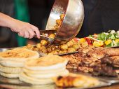 stock photo of buffet  - Buffet stall with grilled meat, potatoes and pancakes dished out