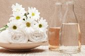 image of fragrance  - bottles with fragrance beside white towels and bunch of margarite flowers - JPG
