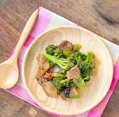 image of pork  - Fried Broccoli and pork in wood plate placed on a wooden table - JPG