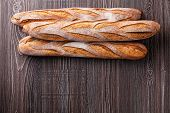 stock photo of baguette  - Three fresh French Baguette on gray wooden background - JPG