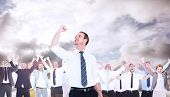 stock photo of clenched fist  - Businessman cheering with clenched fist against blue sky with white clouds - JPG