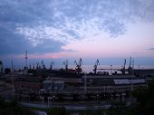 stock photo of distort  - View of a cargo seaport against the evening cloudy sky with wide angle distortion view - JPG