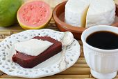 foto of juliet  - Brazilian dessert Romeo and Juliet on white plate goiabada and Minas cheese with cup of coffee and fresh goiaba on wooden table bamboo - JPG