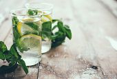 picture of mint-green  - Homemade lemonade refreshing summer detox drink made from lemon and mint in glasses on old vintage wooden board.