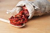 picture of sleeping bag  - Dried tomatoes got enough sleep from canvas bag at wooden background - JPG
