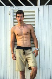 pic of macho man  - Handsome and muscular athletic shirtless young man standing against white beach changing room wall - JPG