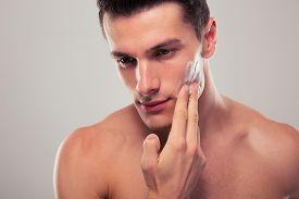 foto of shaved head  - Handsome man applying facial cream over gray background - JPG