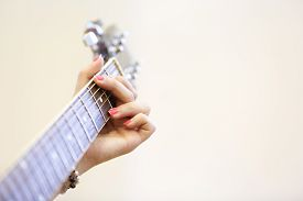 stock photo of woman g-string  - Woman musician holding a guitar learning playing a G chord - JPG