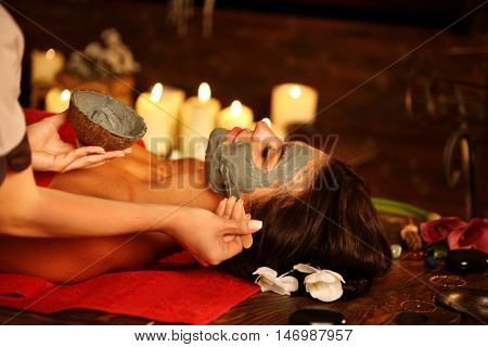 poster of Young woman lying on wooden spa bed. Massage and clay facial mask in spa salon. Girl on candles back