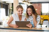 Two happy smiling young women in a cafeteria using digital tablet. Happy girls friends sitting at co poster