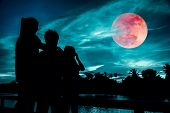 Silhouette Of Mother And Children Looking At Red Super Moon Or Blood Moon On Colorful Sky With Cloud poster