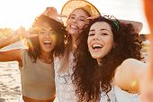 Three joyful multiethnic women 20s in summer clothing smiling at camera while taking selfie photo du poster