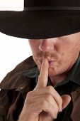 image of shh  - A close up of a cowboy with his finger up to his lips saying shh - JPG