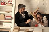 Home Schooling. Girl With Glasses And Bearded Man Sit At Desk And Fight With Scrolls. Father And Sch poster