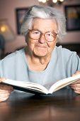 foto of elderly woman  - Adorable elderly woman reading a book at home - JPG