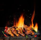 Delicious pieces of chicken meat on grill with Fire flames. Isolated on black background. Barbecue a poster