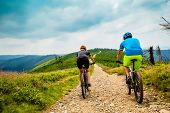 Cycling women and man riding on bikes at  mountains trail landscape. Couple cycling MTB enduro flow  poster