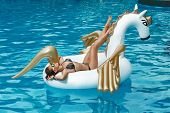 Tan girl lies on inflatable mattress white unicorn in the pool poster