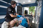 picture of triage  - EMT professional check pulse on elderly woman in ambulance - JPG