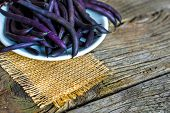 Purple String Beans On A Wooden Plate On A Wooden Background poster