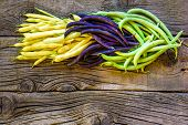 Collection Of Green, Yellow And Purple Bush Beans, Opened Green Peas On Wooden Background poster