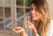 Beautiful young woman smiling and eating nuts at home. Healthy concept. poster