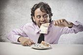 Постер, плакат: Жадный бизнесмен едят банкноты из блюдо