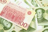 A Close Up Image Of A One Hundred Mexican Peso Bank Note With Chinese One Yuan Bills In Macro poster