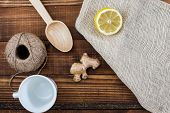 Rustic table top view with wooden spoon, cord,  tea cup and ginger poster